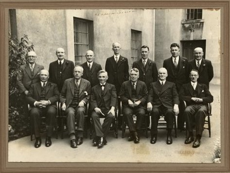 The Labour government of New Zealand that would commission the Thomas Report. In 1935 Rex Mason was not yet Minister of Education [back row, 4th from left]. The future Prime Minister, Fraser is 2nd from left, front row. Photograph taken by A W Schaef. Gustafson, Barry. Ref: PAColl-3222-3-002. Alexander Turnbull Library, Wellington, New Zealand. http://natlib.govt.nz/records/22641171